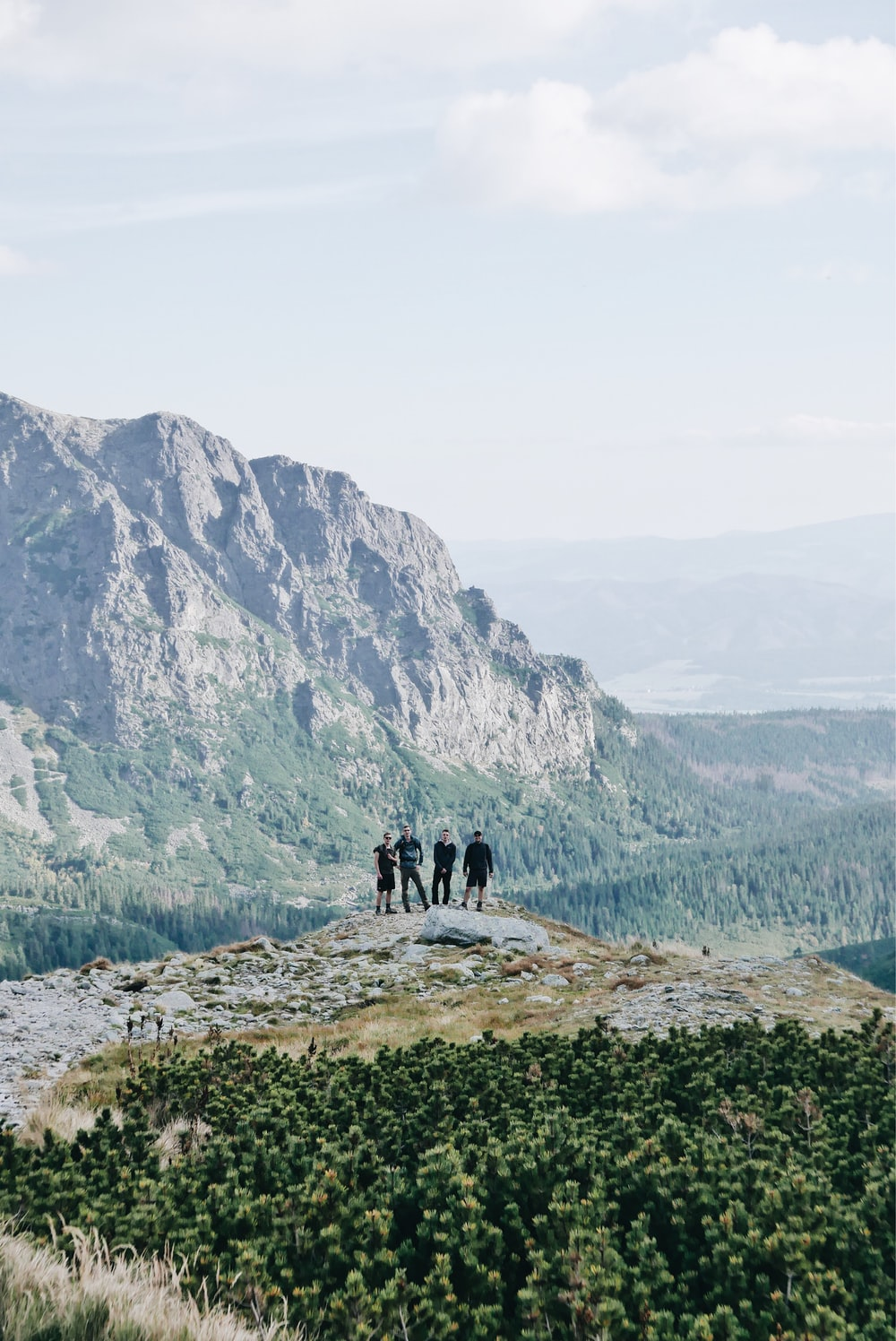 photography of four persons on mountain