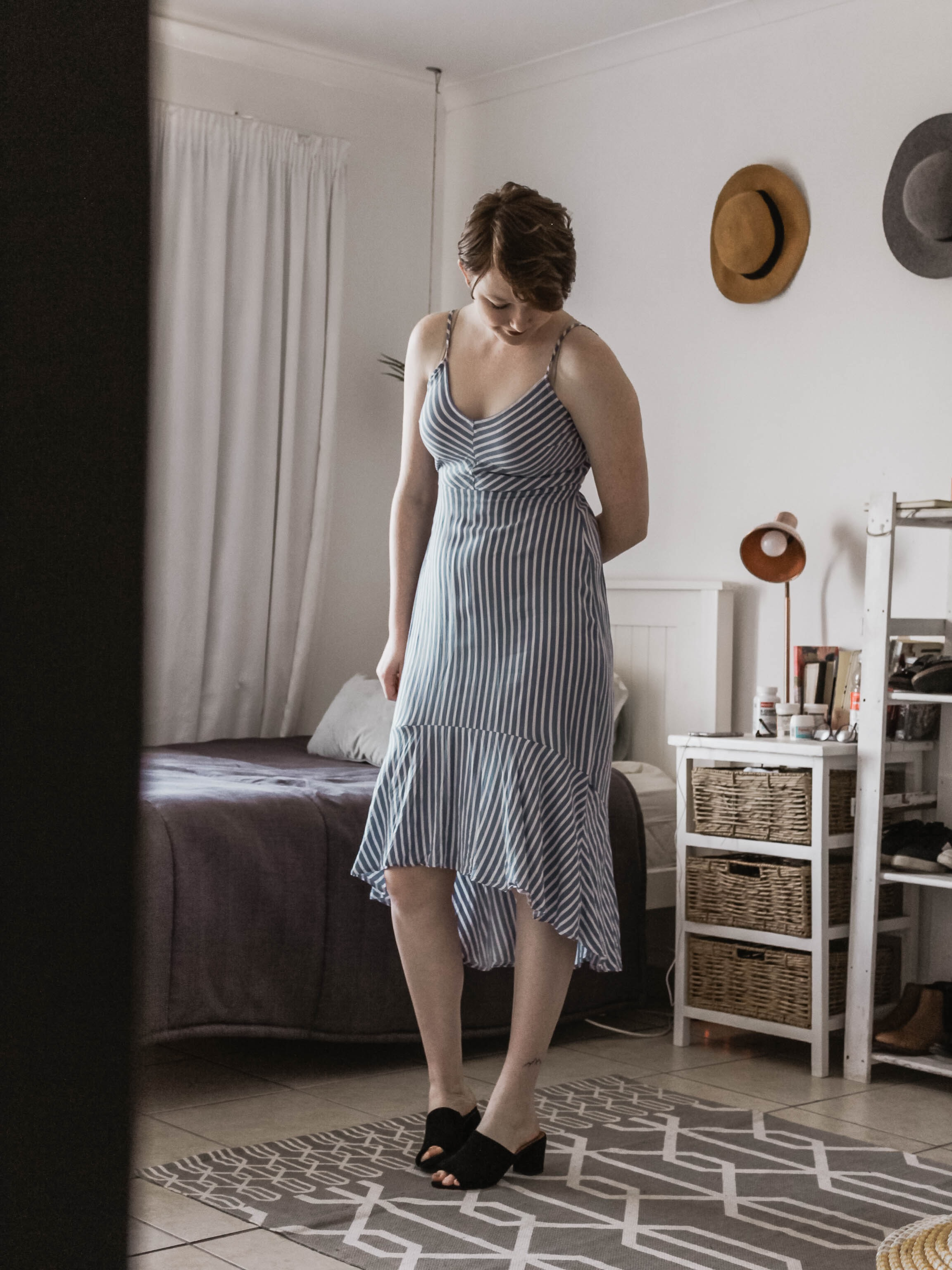 woman wearing black and white striped spaghetti strap dress standing beside bed frame