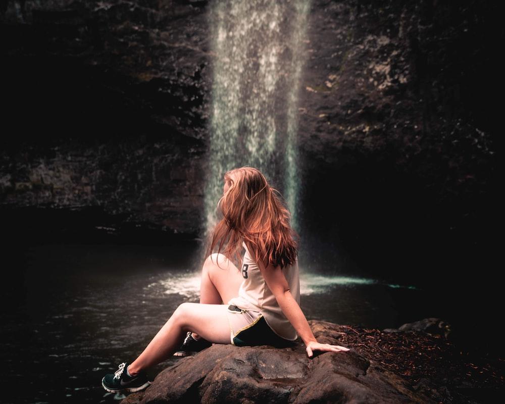 woman sitting on rock near waterfalls