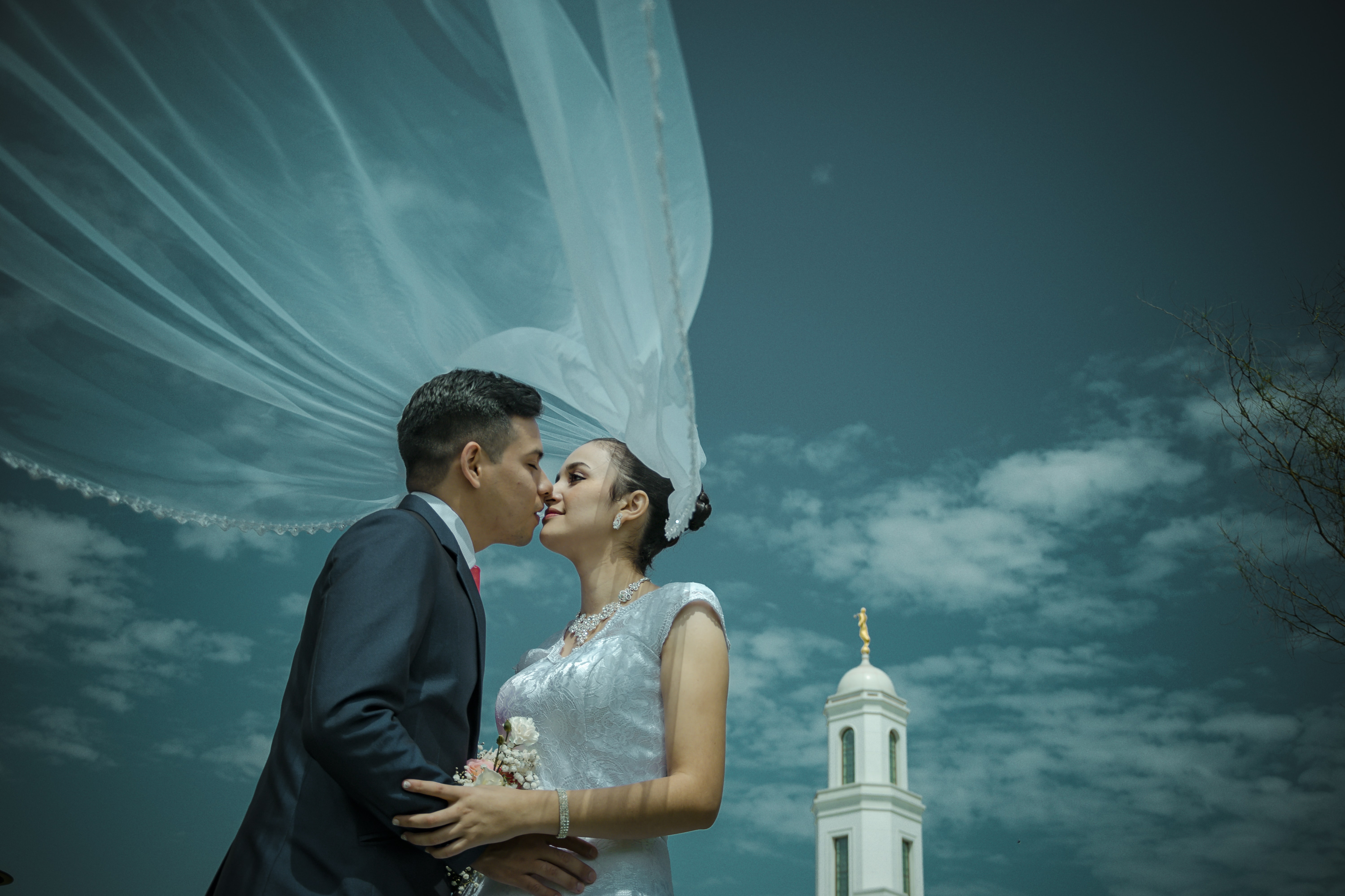 man and woman kissing near white tower