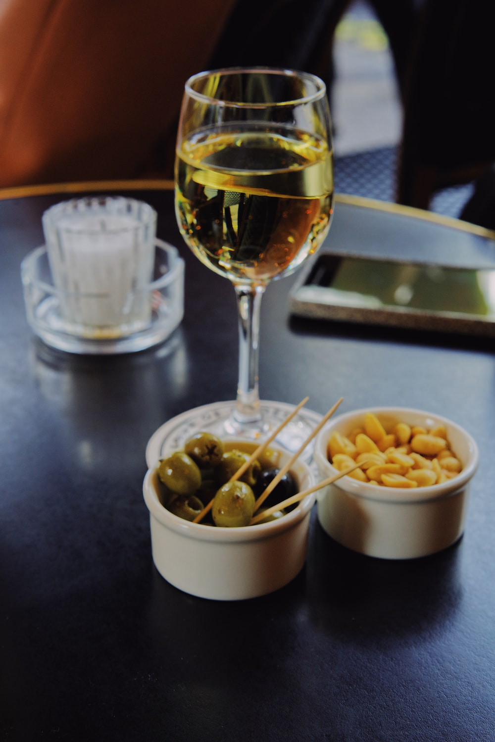 clear wine glass, brown peanuts, and round gray fruits
