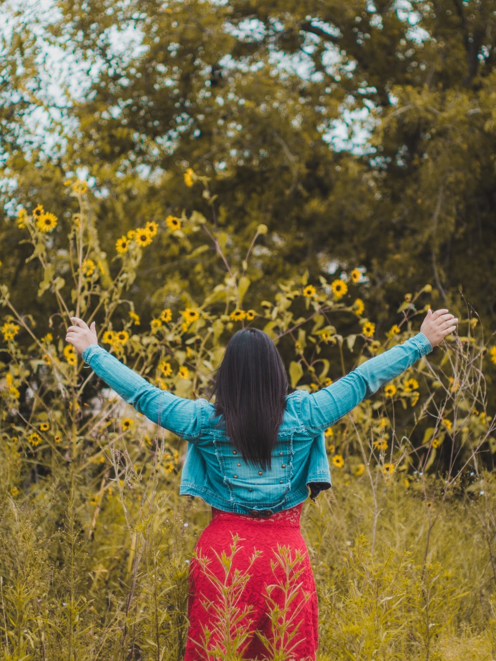 woman raising two hands in front of yellow sunflowers