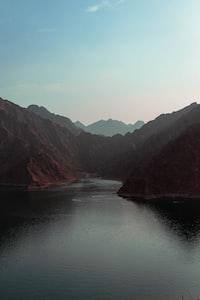 lake near mountain at daytime