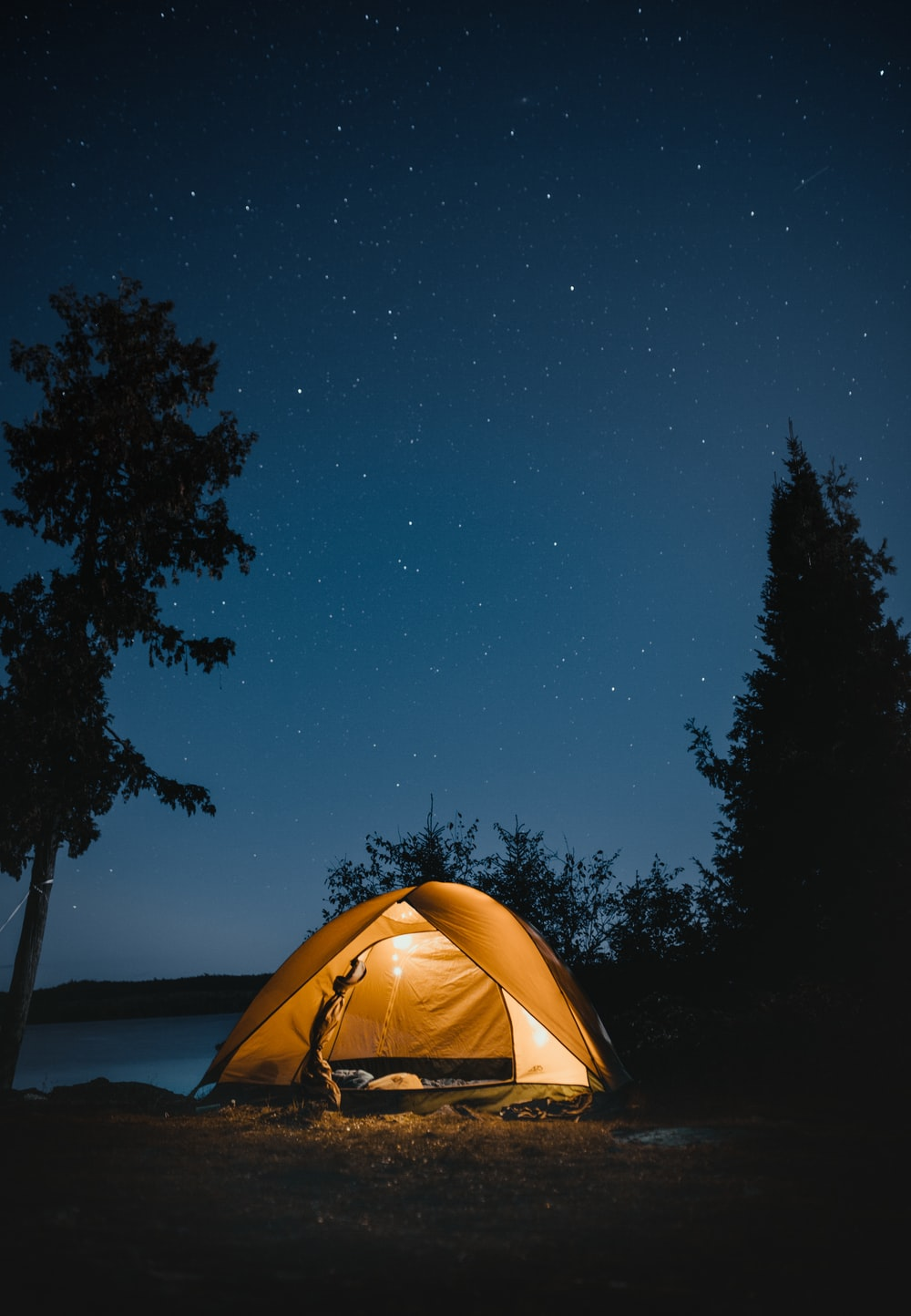 brown dome tent near trees at night