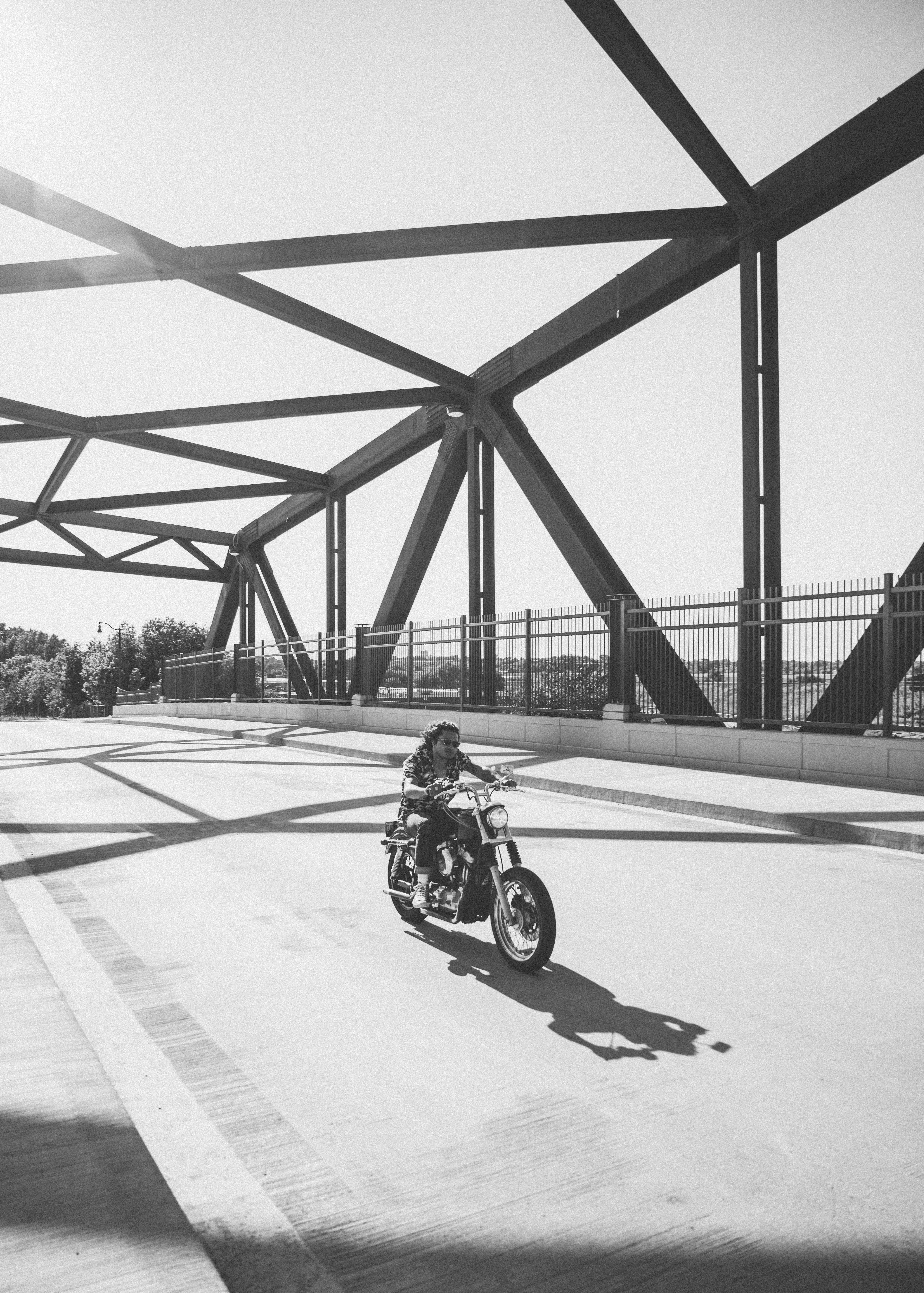 grayscale photo of man riding motorcycle on bridge