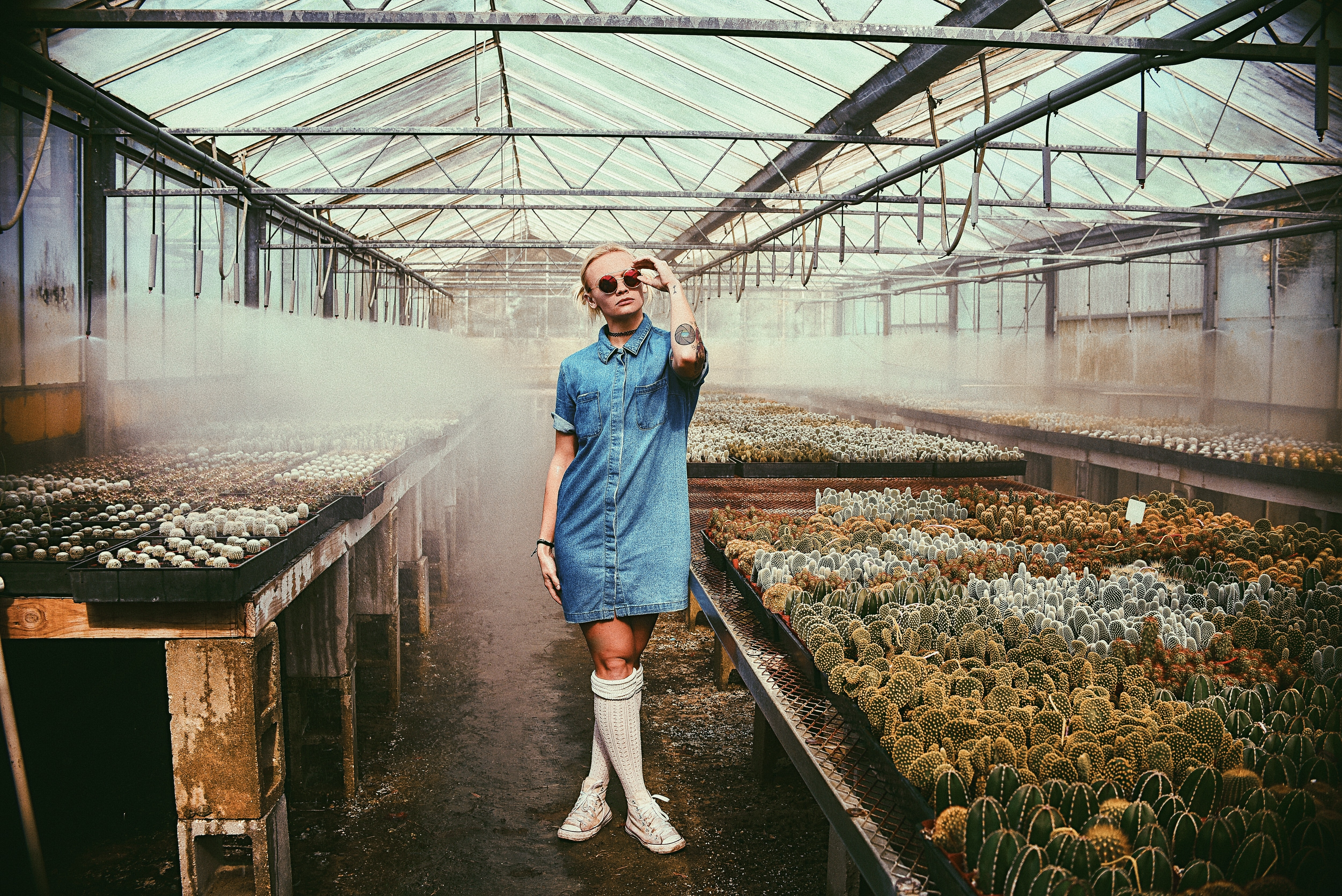 woman standing beside cacti holding sunglasses inside greenhouse