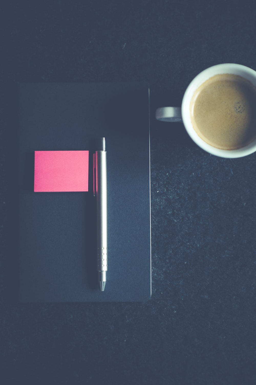 click pen on book beside the mug