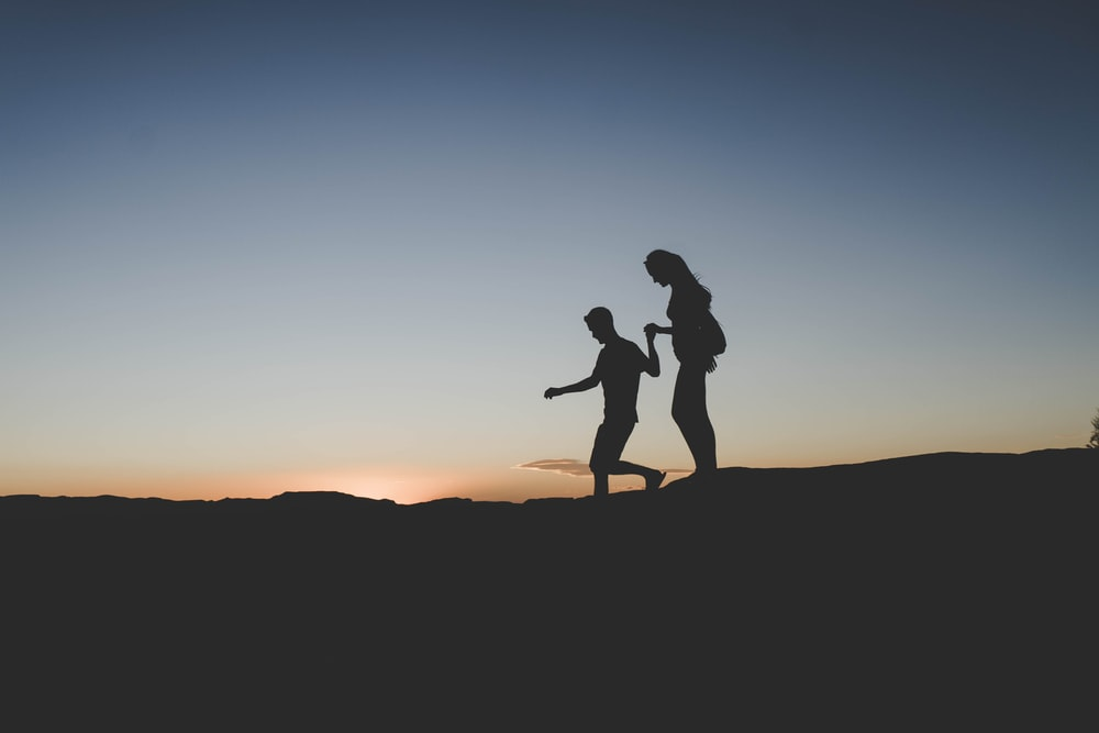 silhouette of man and woman walking on mountain
