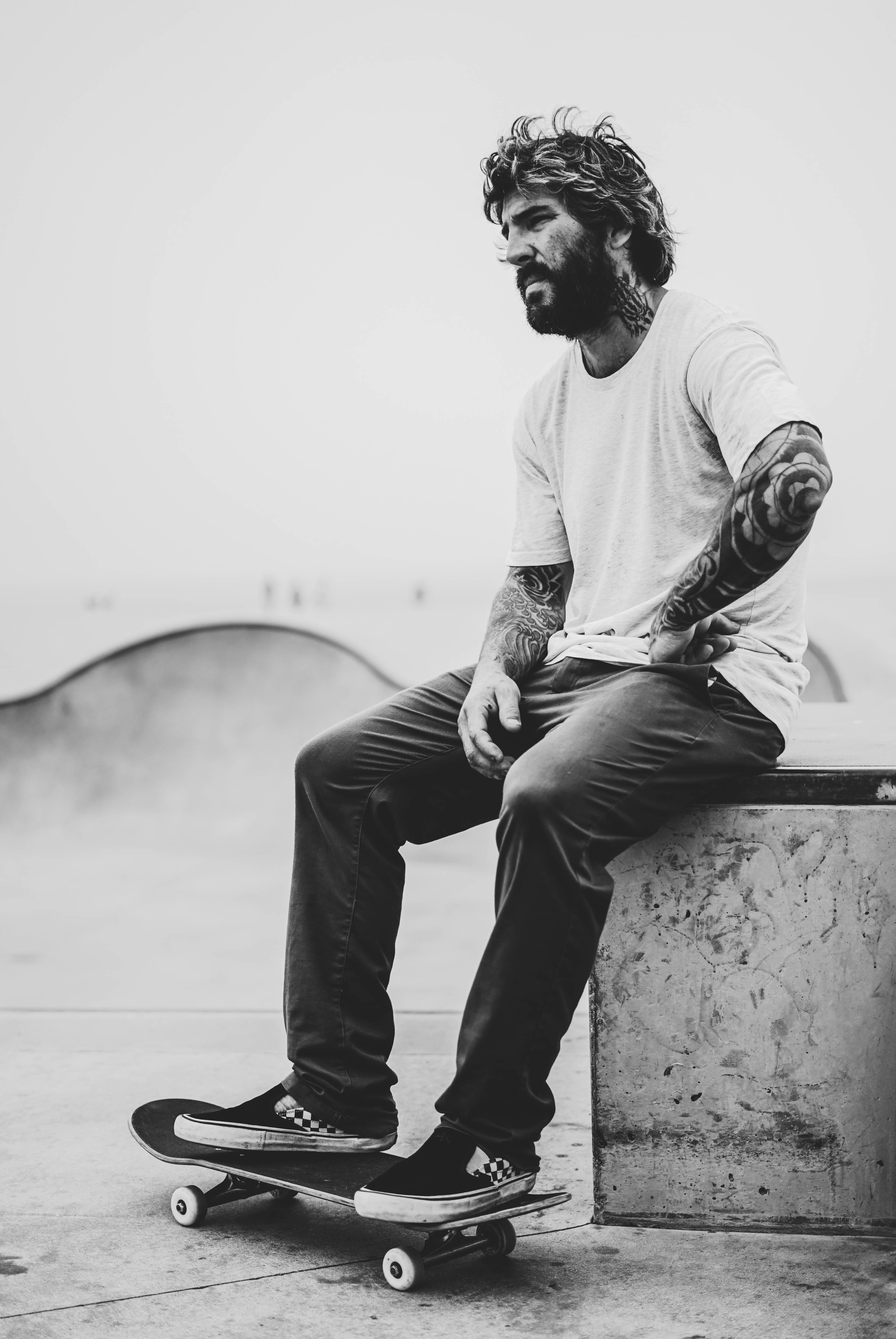 grayscale photography of man sitting on bench while his feet on skateboard