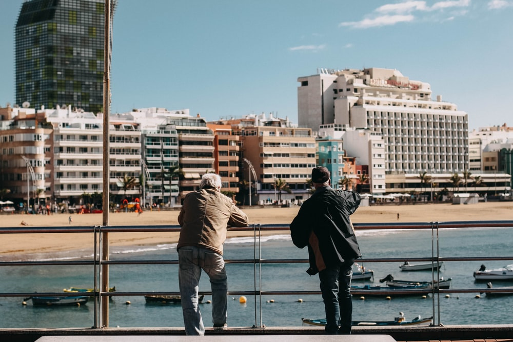two men leaning on metal rails