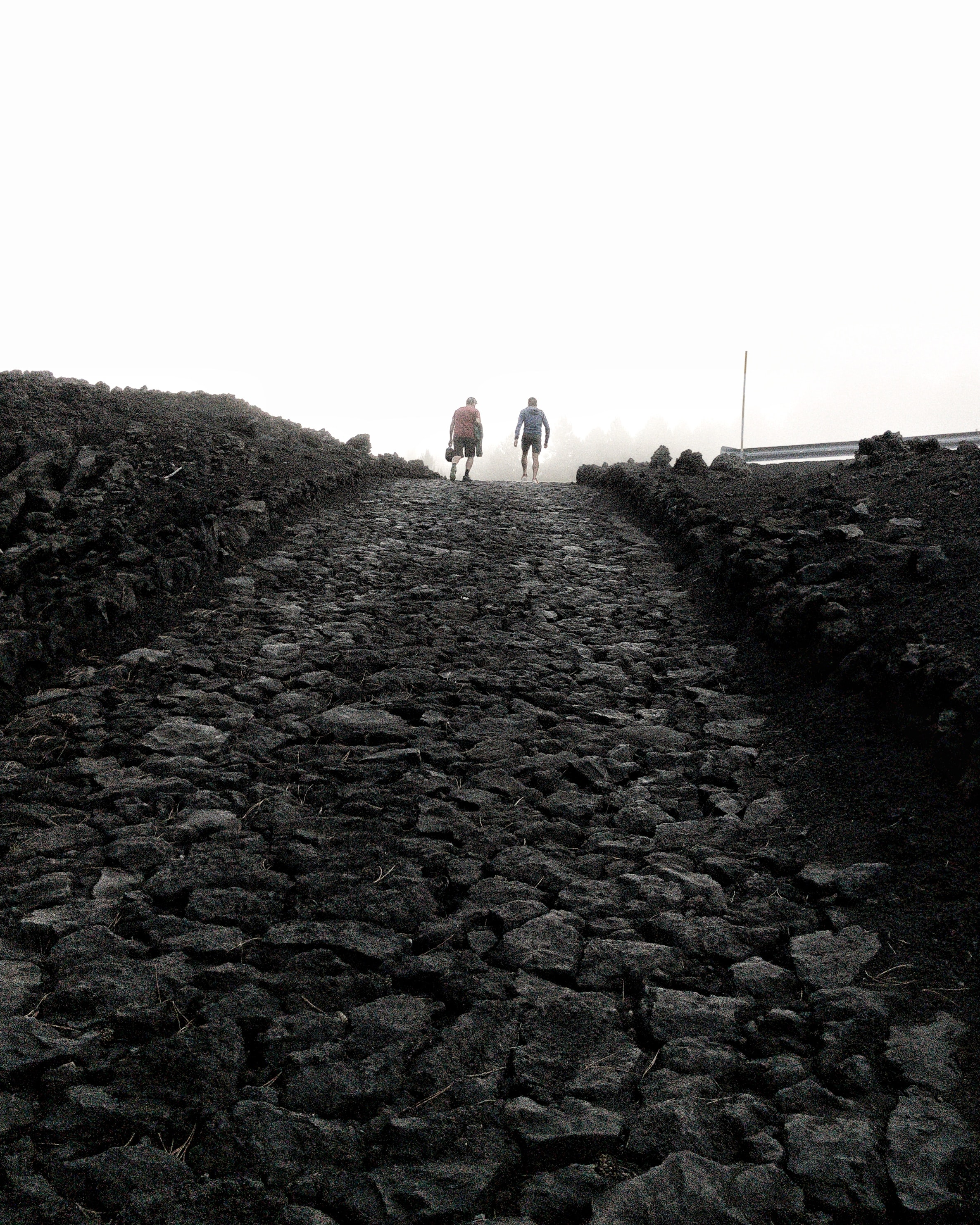 photo of two persons walking on rocky pathway