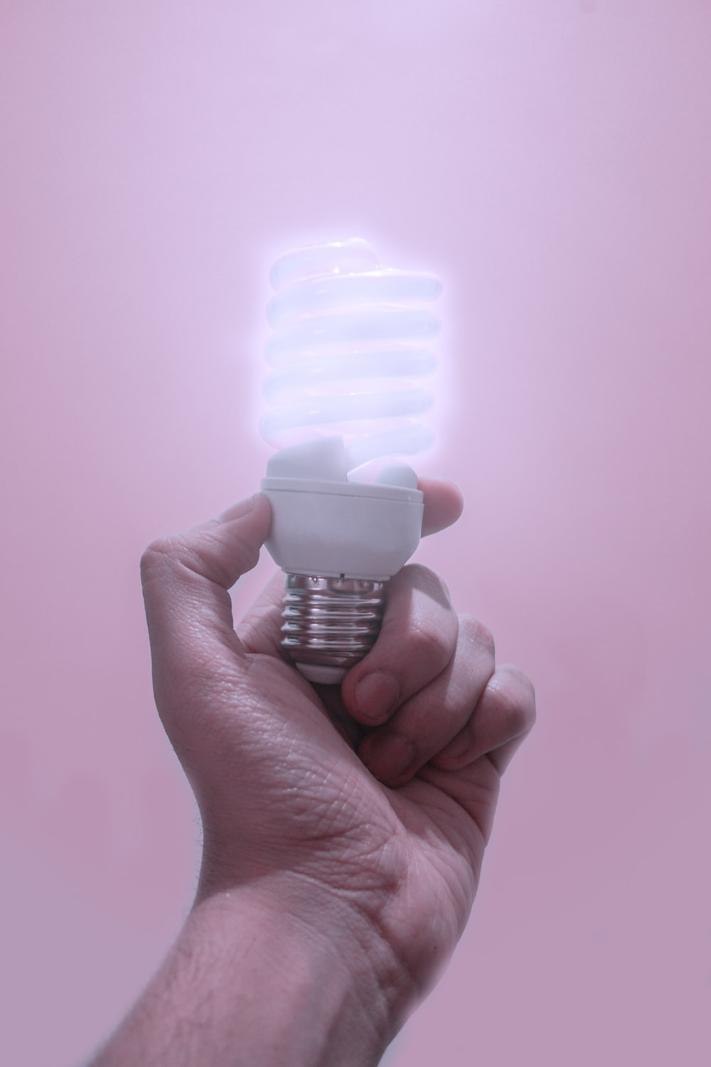 person holding CFL light bulb turned-on