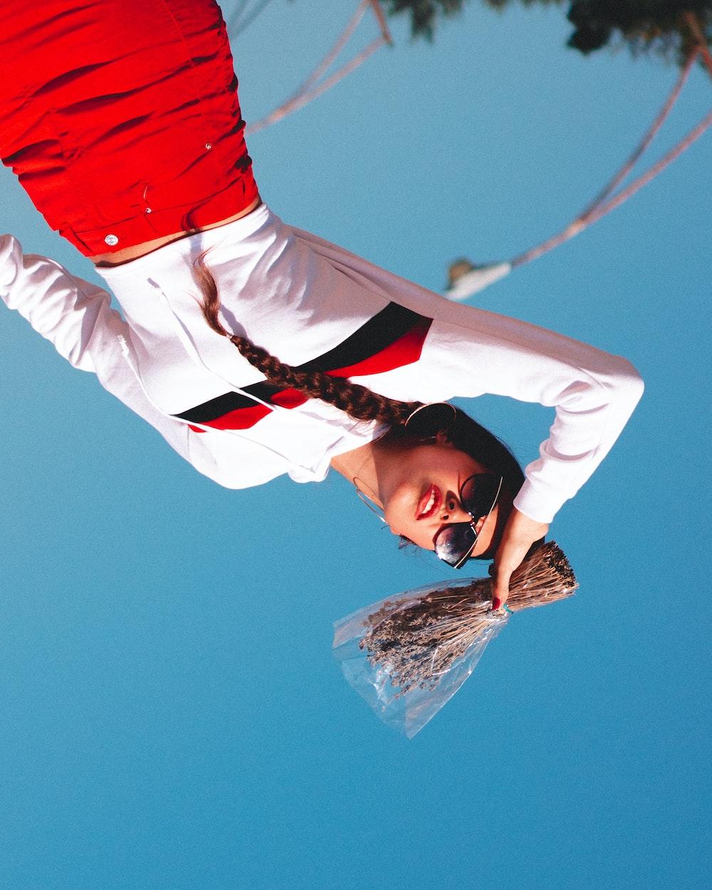 woman holding brown vine bundle under blue sky