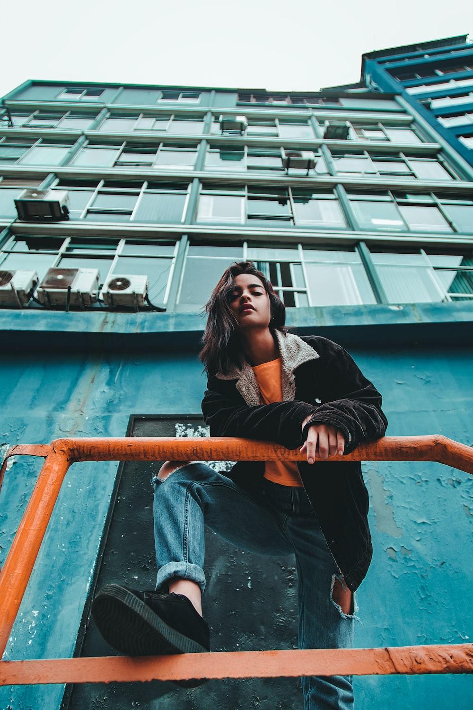 woman standing near orange metal railing on green concrete building