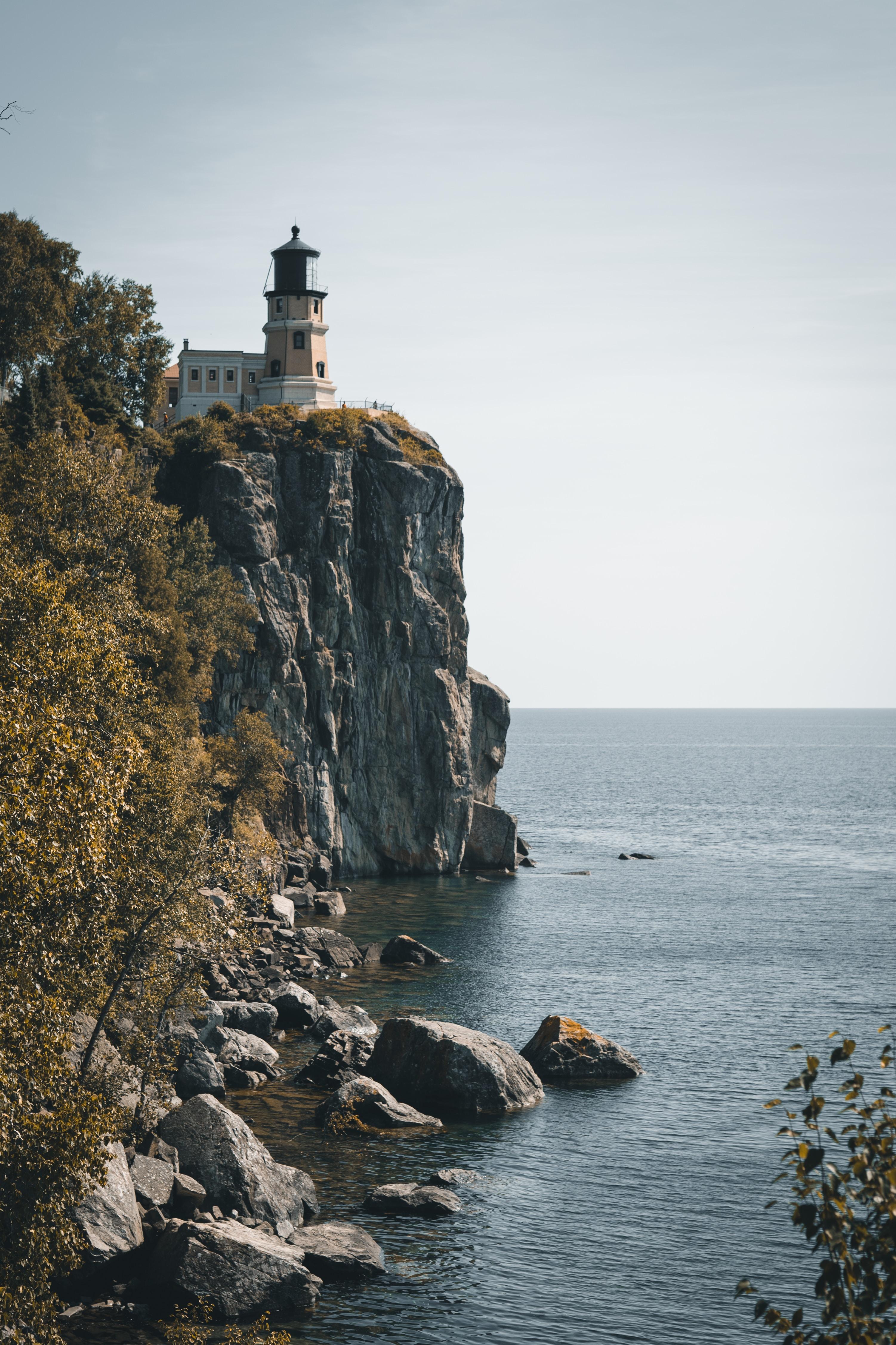lighthouse above cliff near seashore