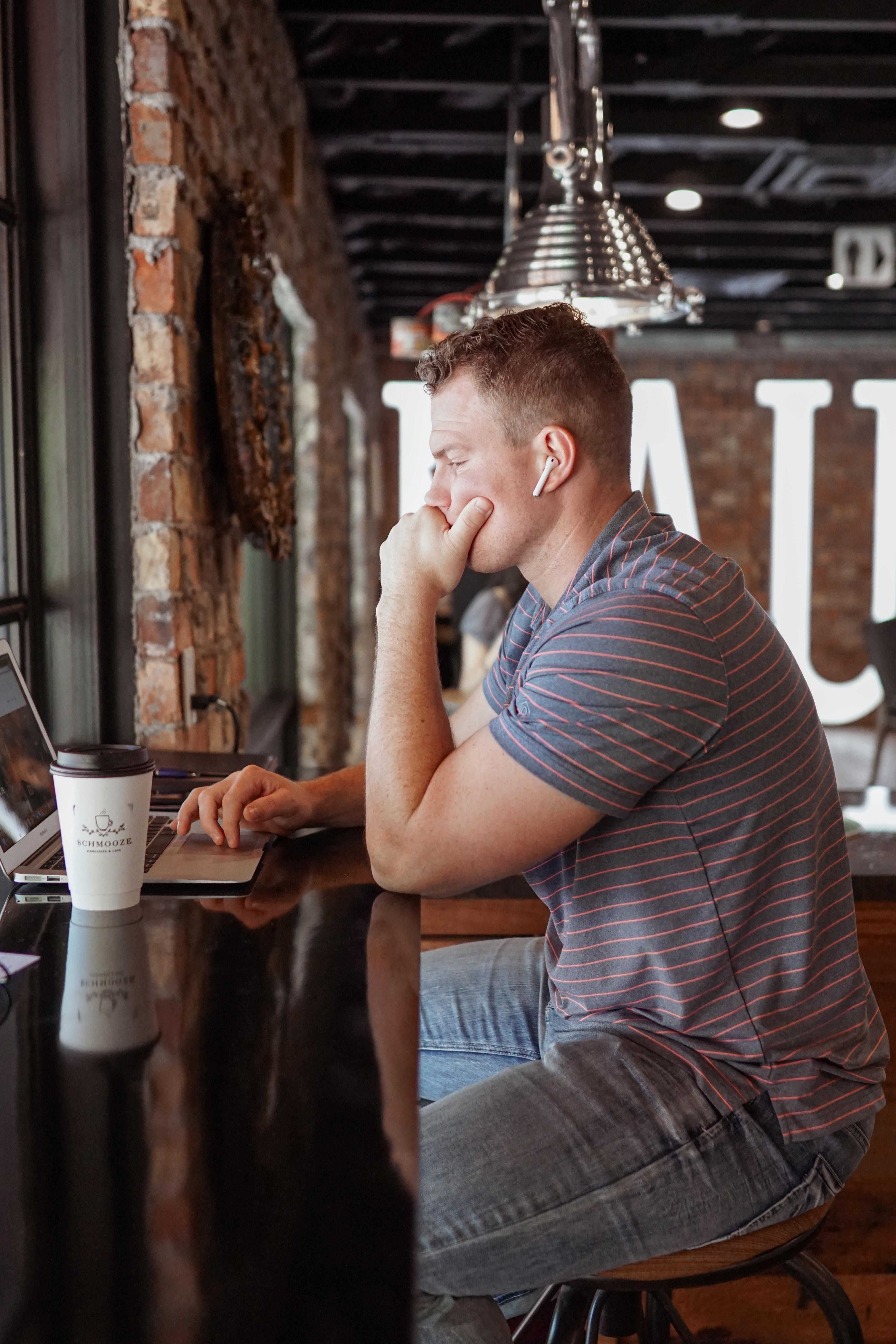 man sitting on chair using gray laptop