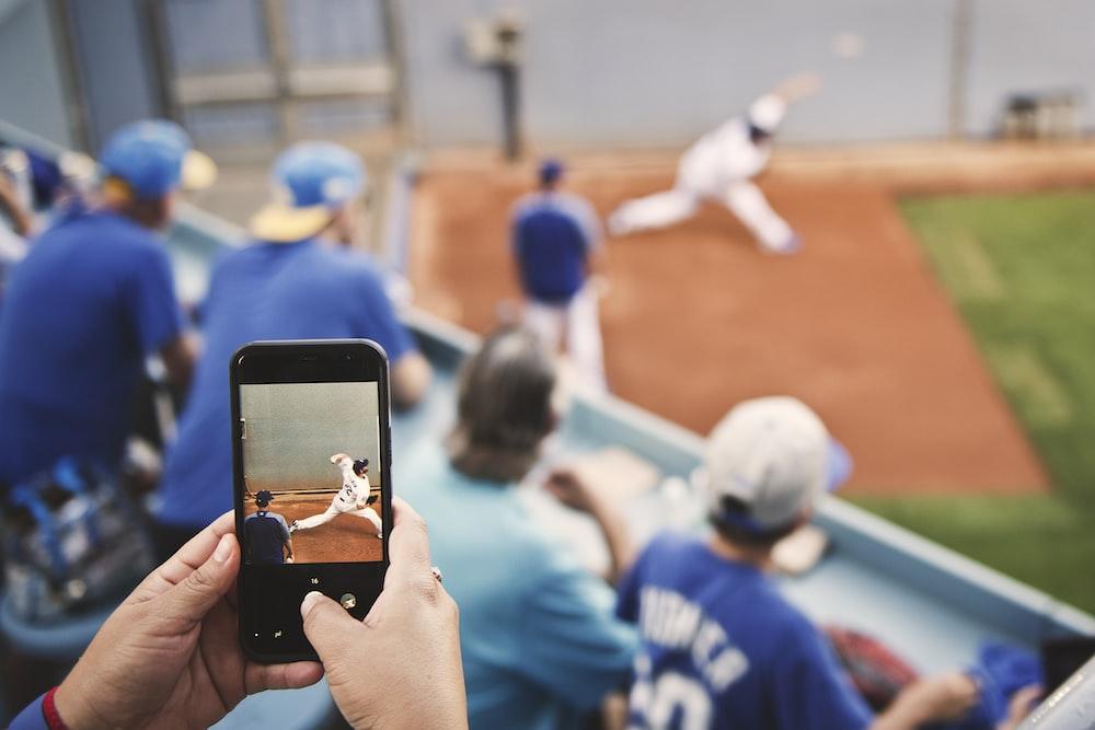 selective focus photo of phone displaying baseball player