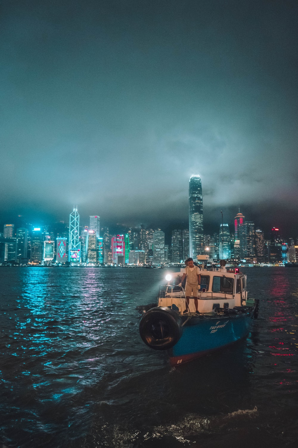 person standing on fishing boat near buildings at night