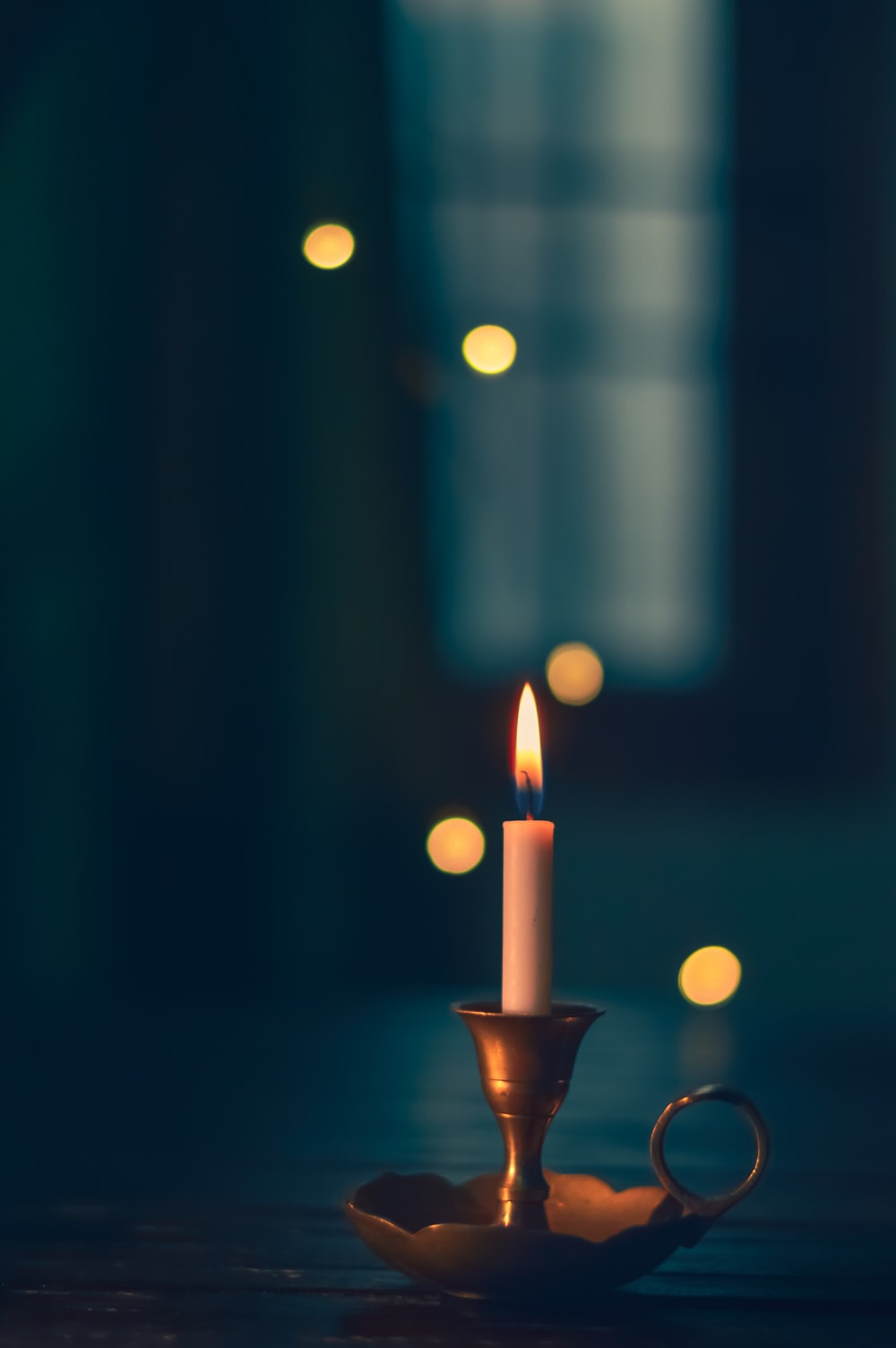 white candle lit on brass candle holder
