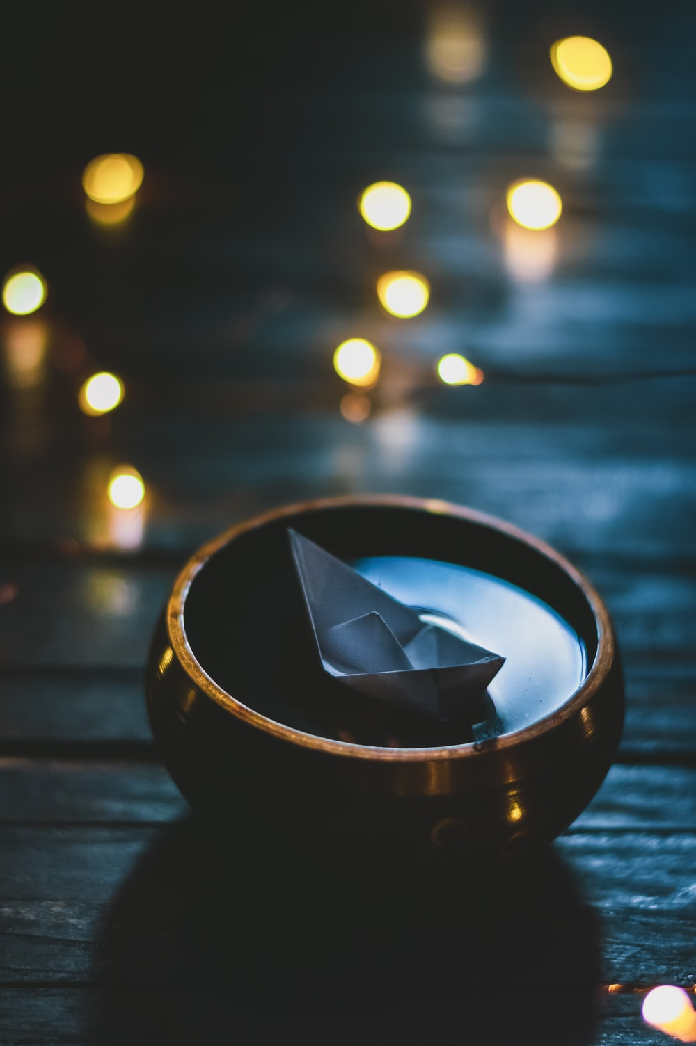selective focus photograph of paper boat on bowl