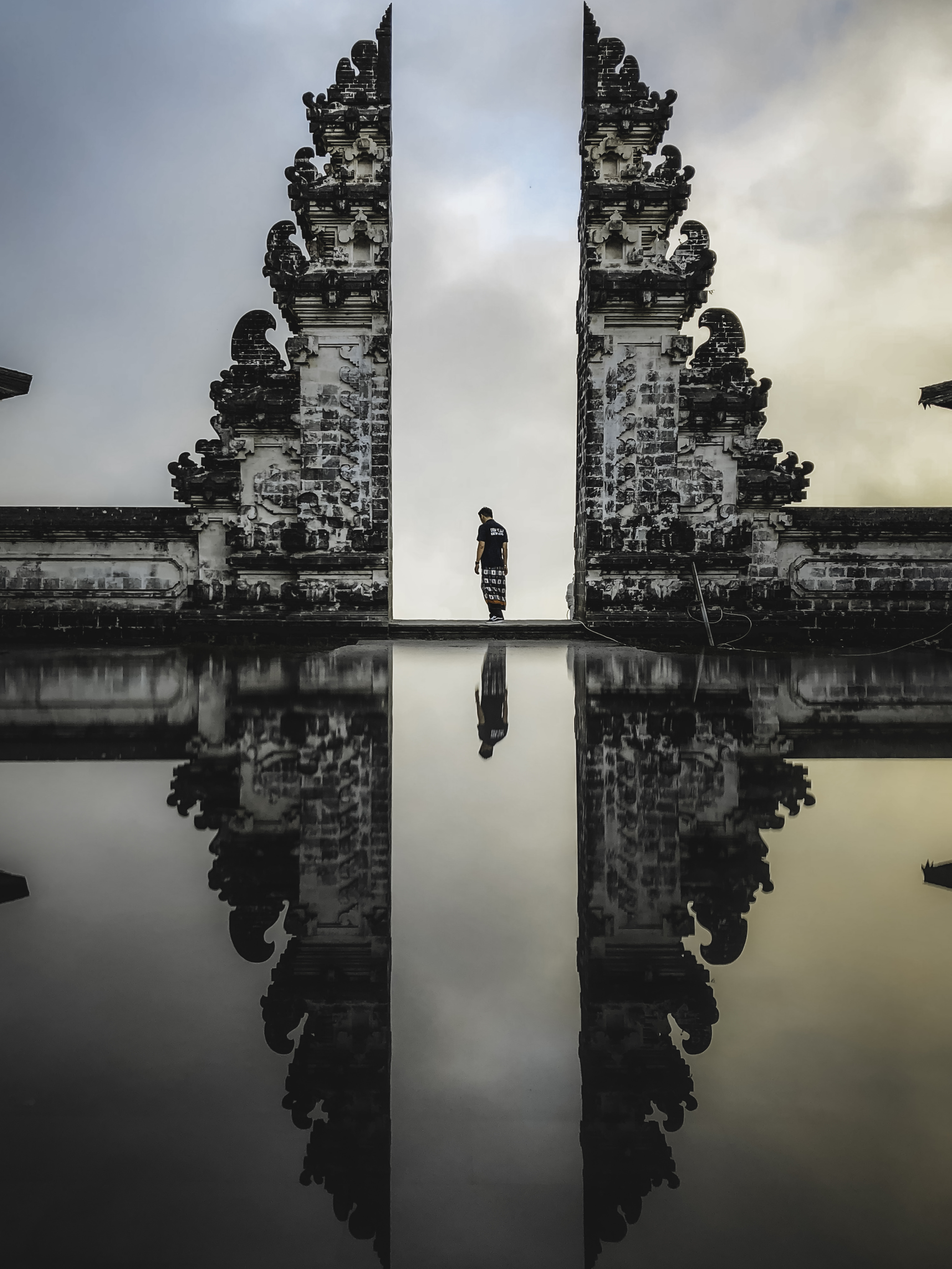 man standing between ruins in reflective photography