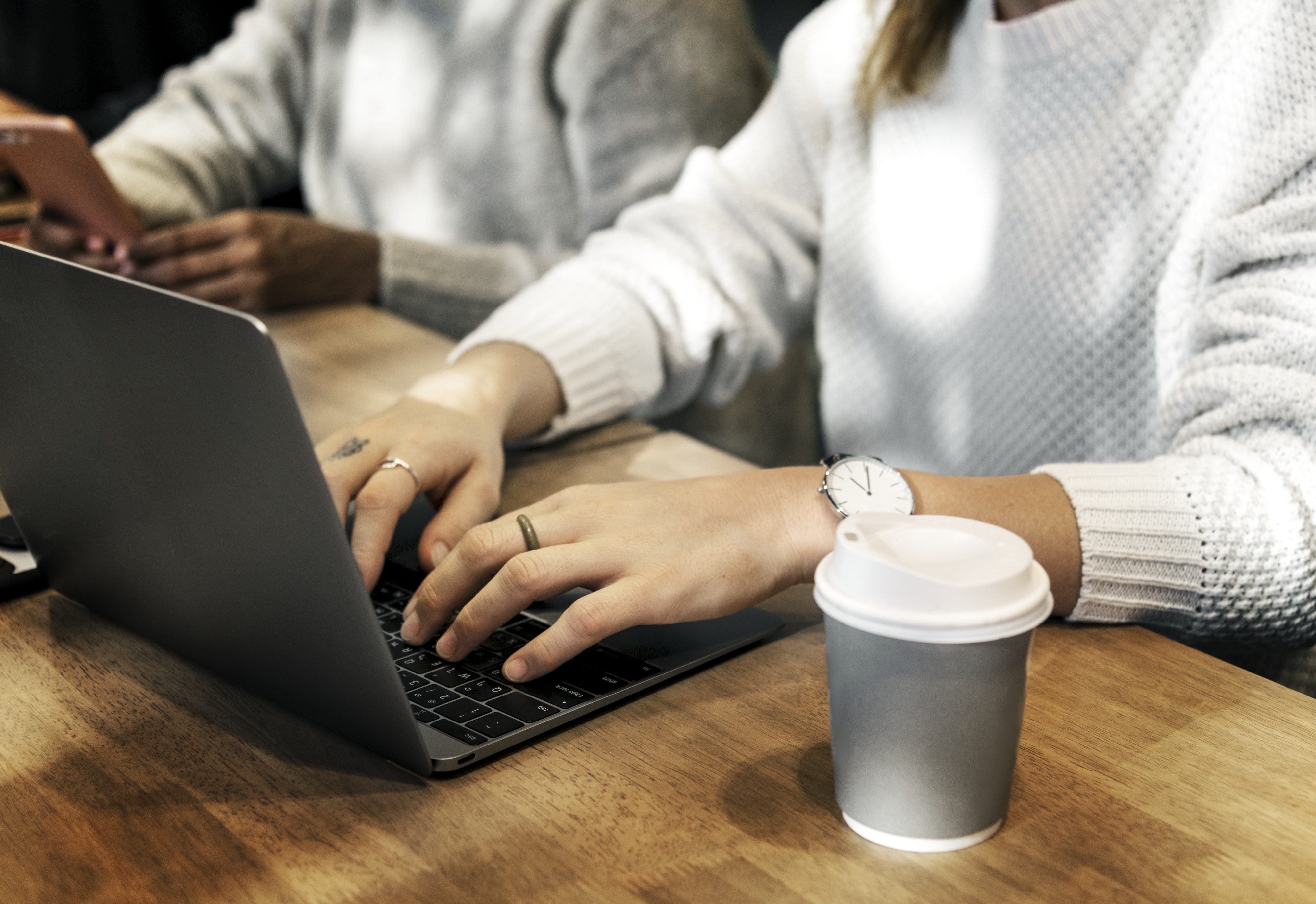 woman using laptop beside grey disposable cup on table