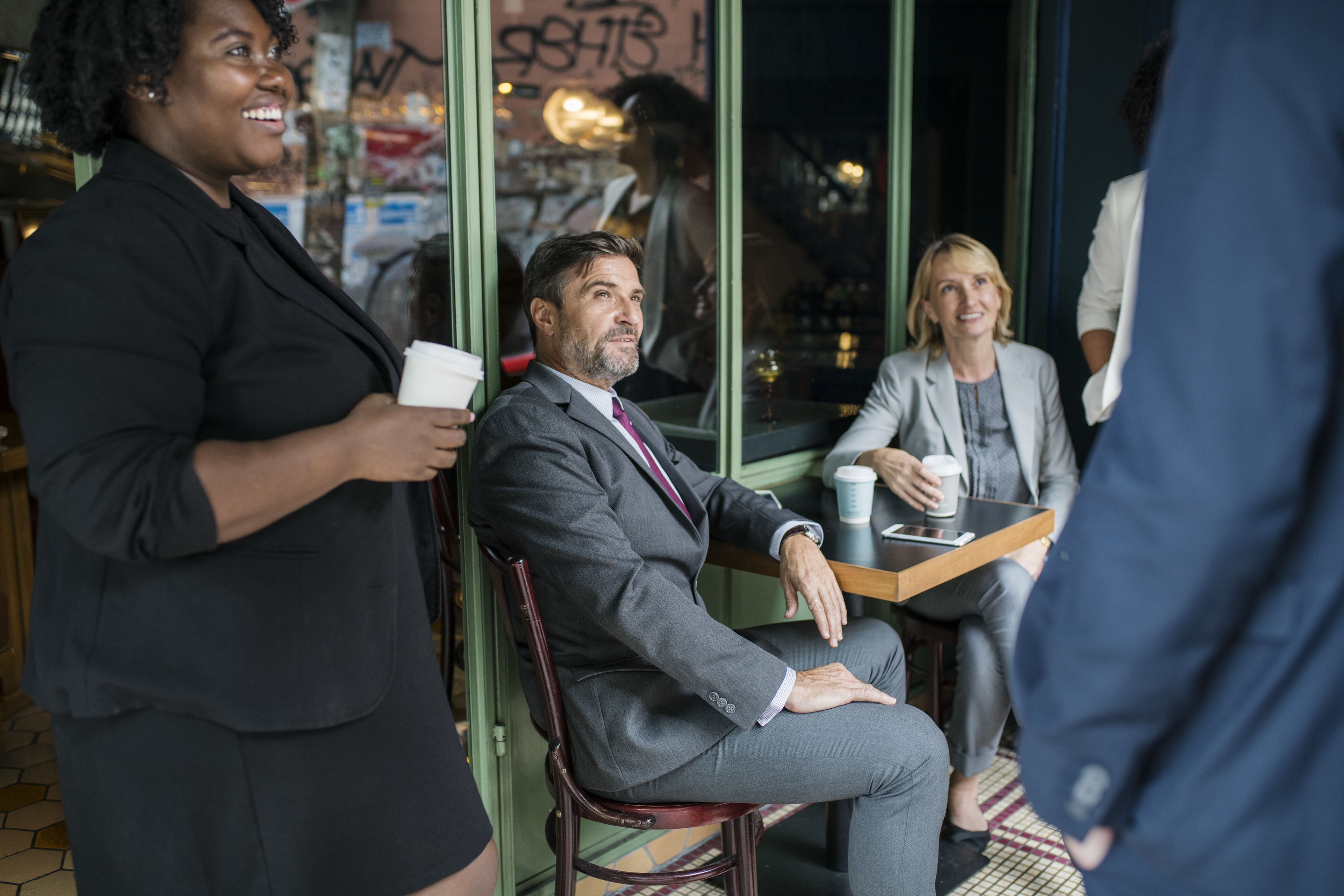 man in gray suit sitting with women