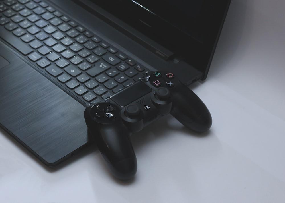 black Sony DualShock 4 controller on black laptop computer