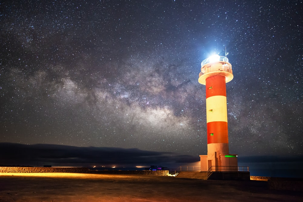 red and white striped lighthouse lighted near shore