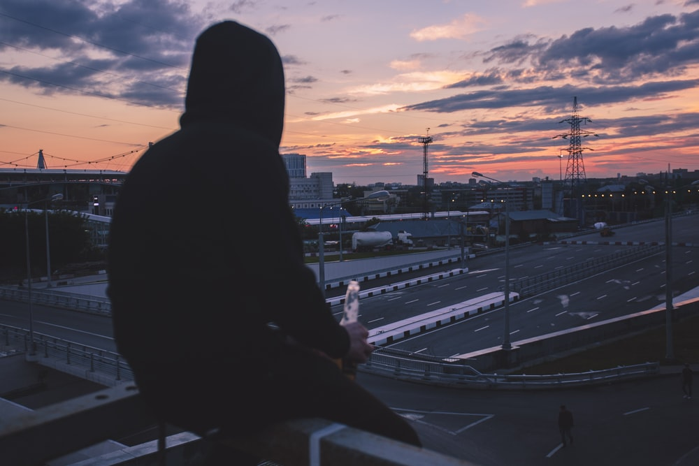 man sitting on handrail front of highway during golden hour
