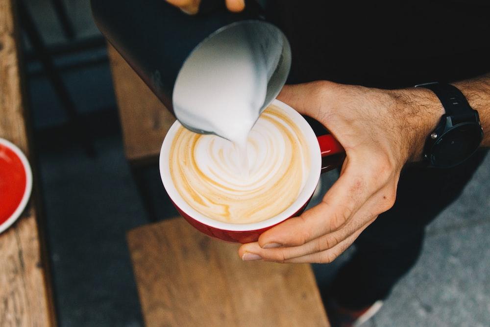 person pouring milk on cappuccino