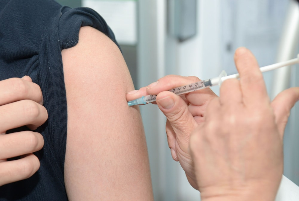 person injecting someone on his arm