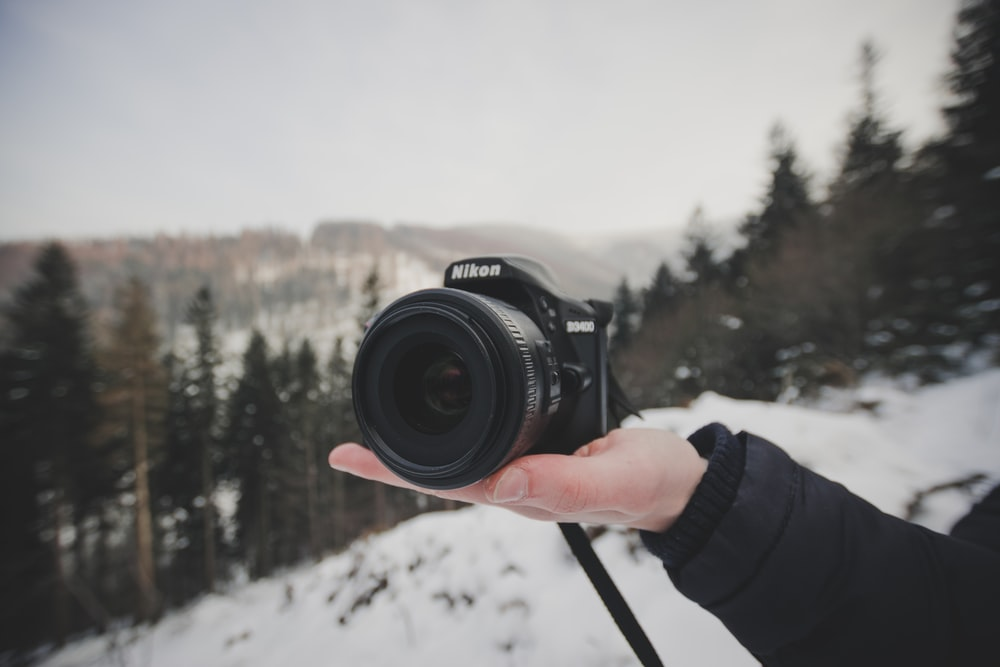 person holding black Nikon camera]