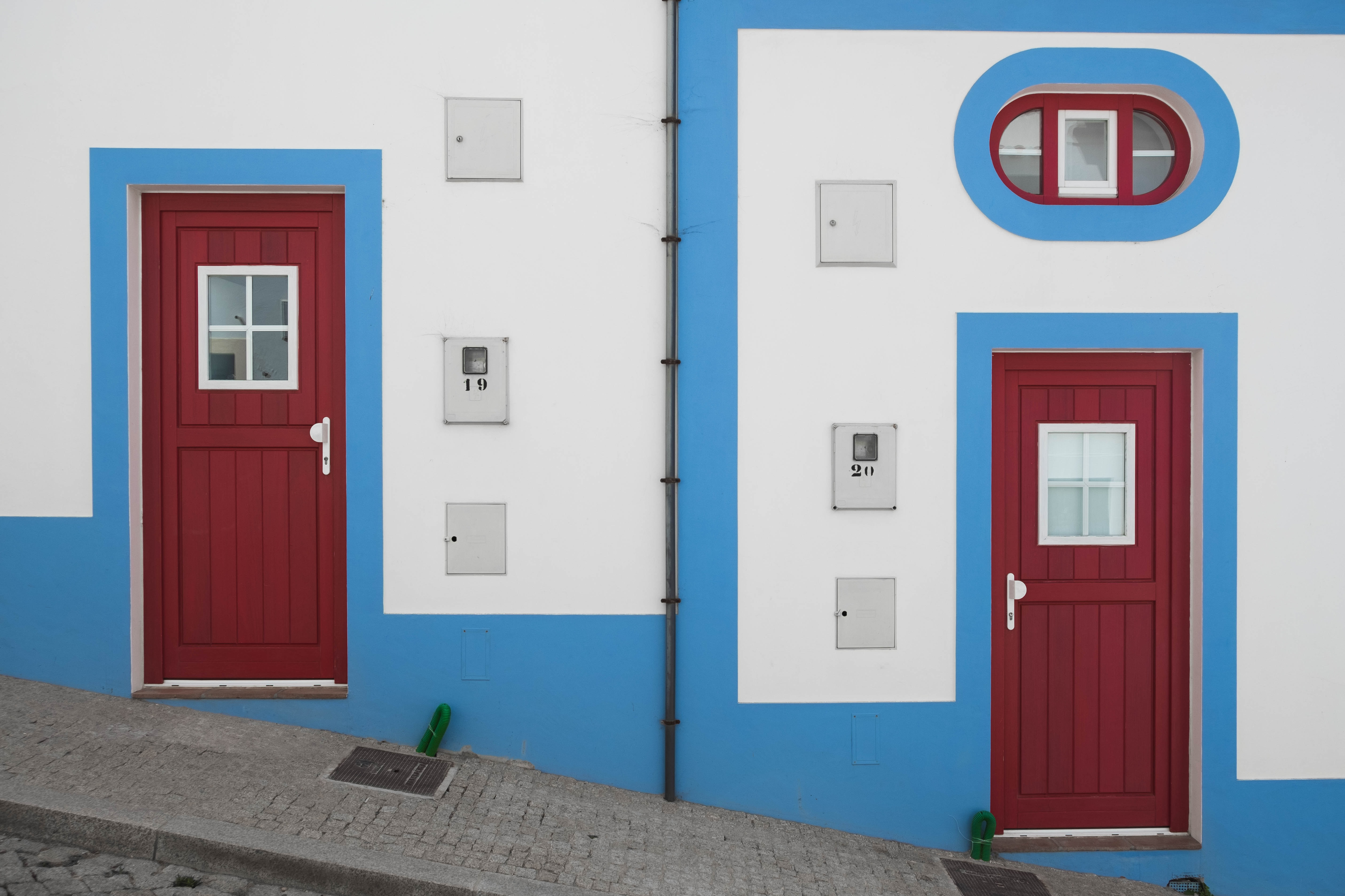 white-blue-and-red houses on inclined street at daytime