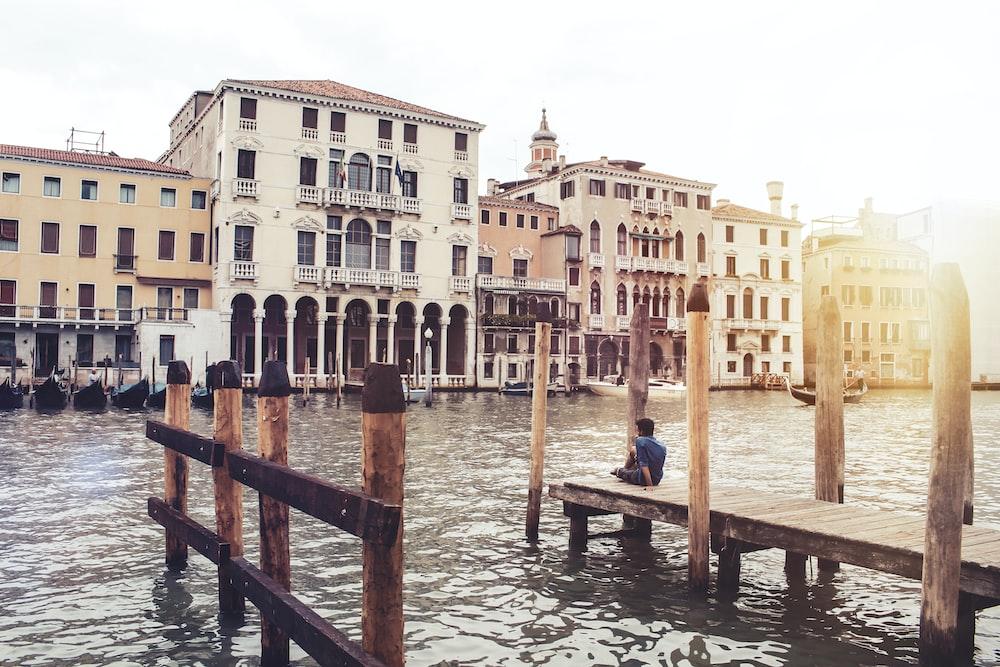 concrete buildings beside body of water