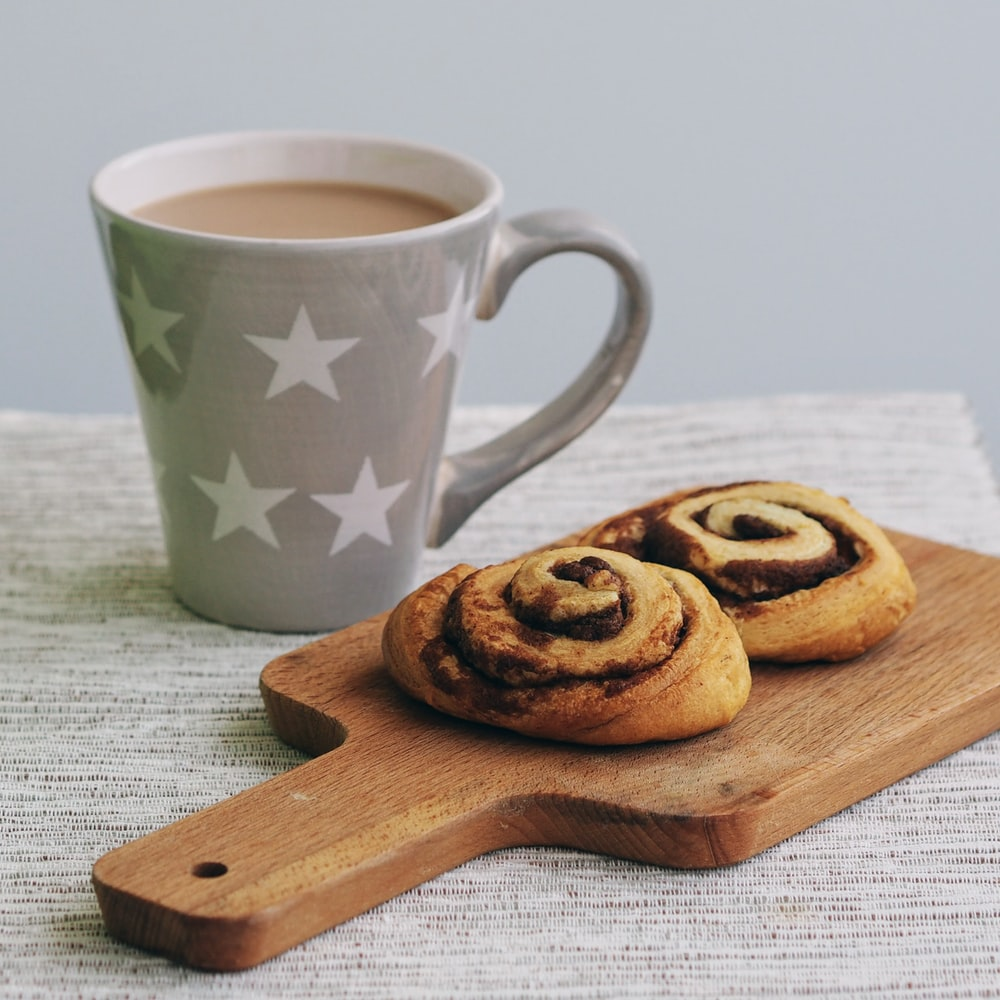 gray and white star print mug and two baked breads