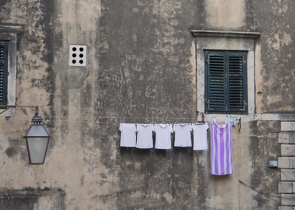 clothes hanged on wire beside window