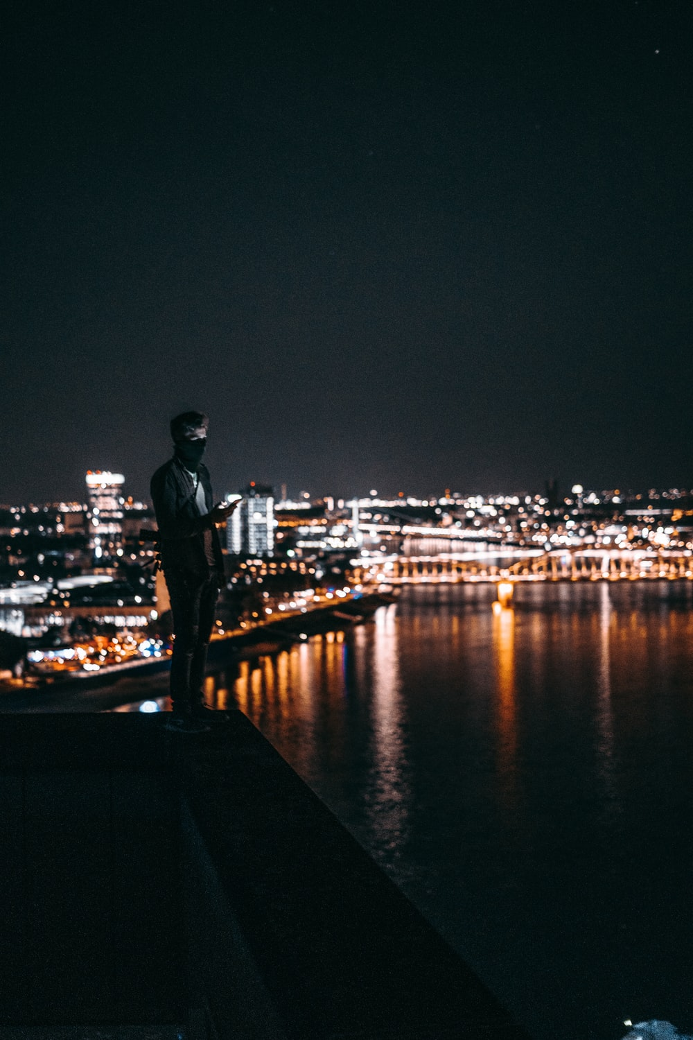 man standing on ledge in front of body of water