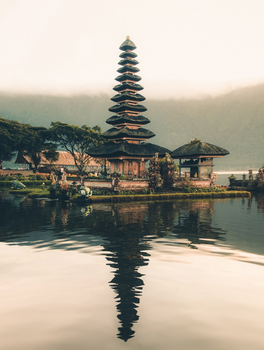 temple beside body of water and trees
