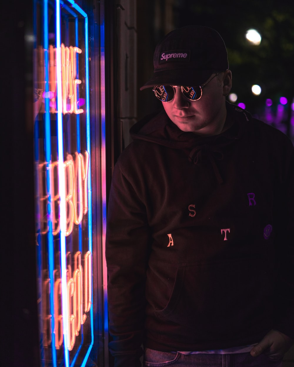 man standing beside neon signage
