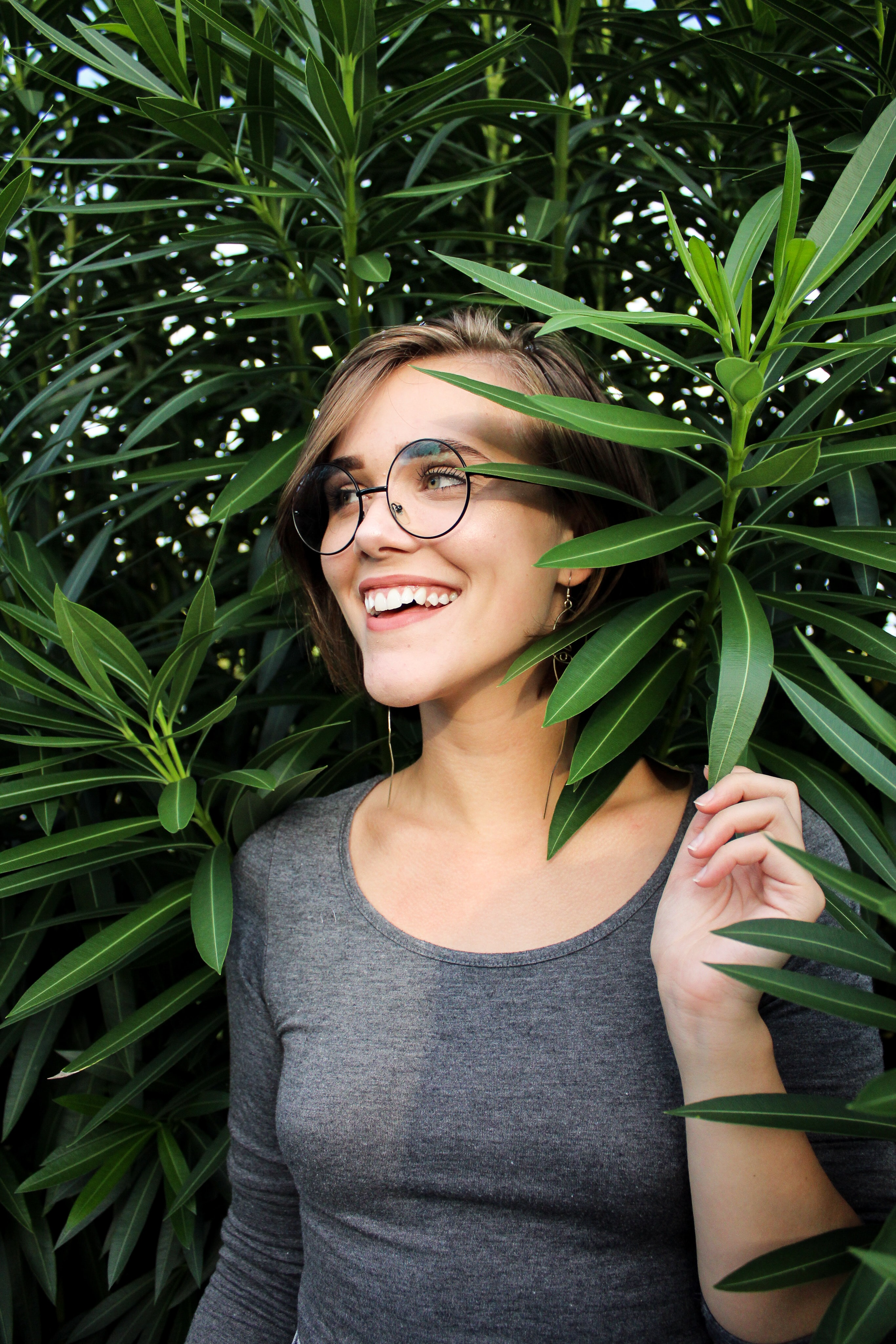 woman holding a green-leafed plant smiling during daytime