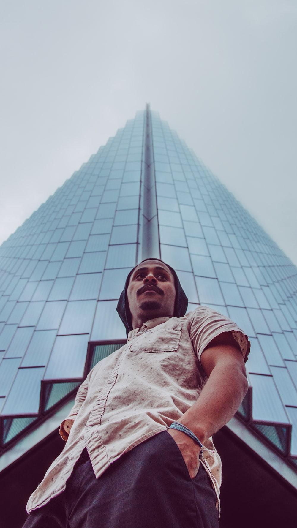 man standing beside building