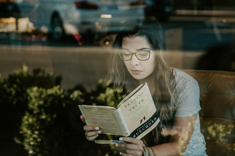 woman wearing black framed eyeglasses reading book