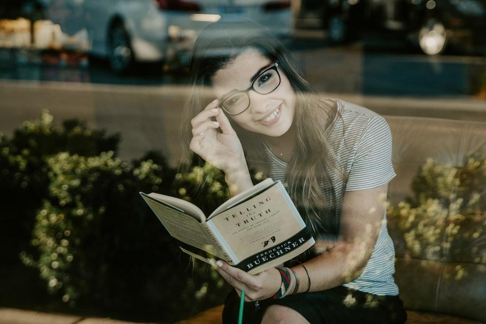 woman smiling wearing black eyeglasses reading book