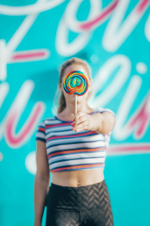 person holding lollipop near wall