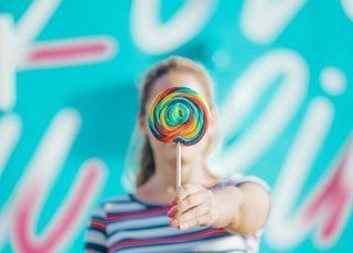 person holding lollipop near wall