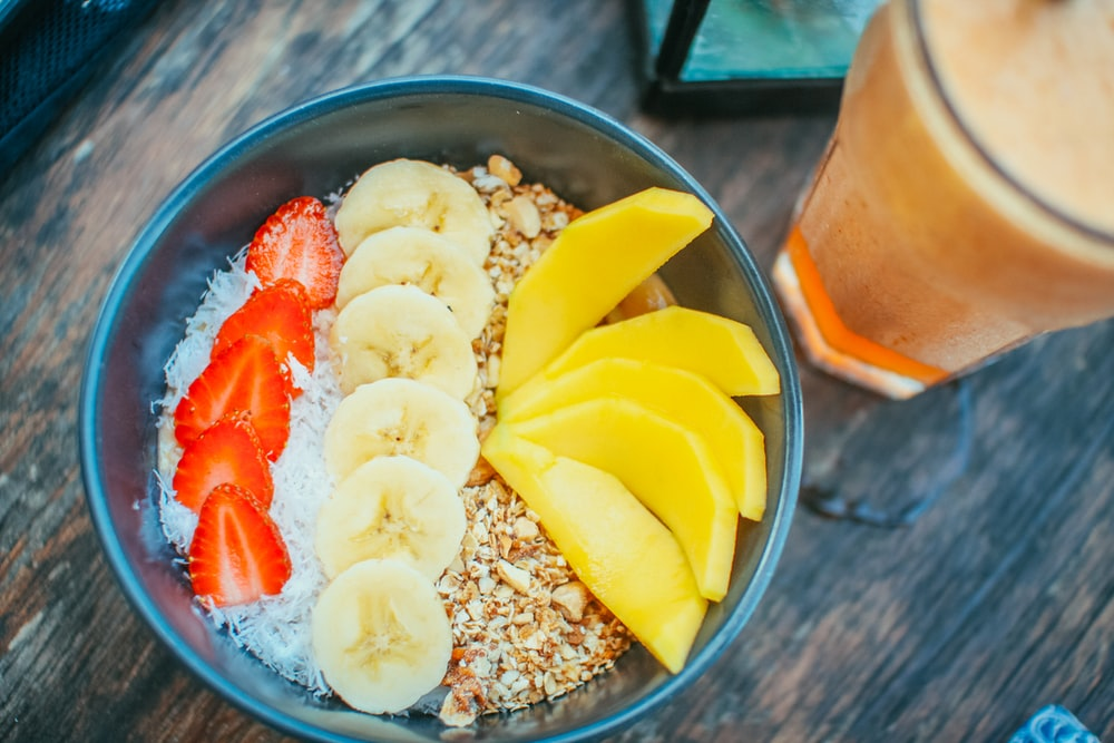 oats with strawberries, bananas, and mangoes in bowl