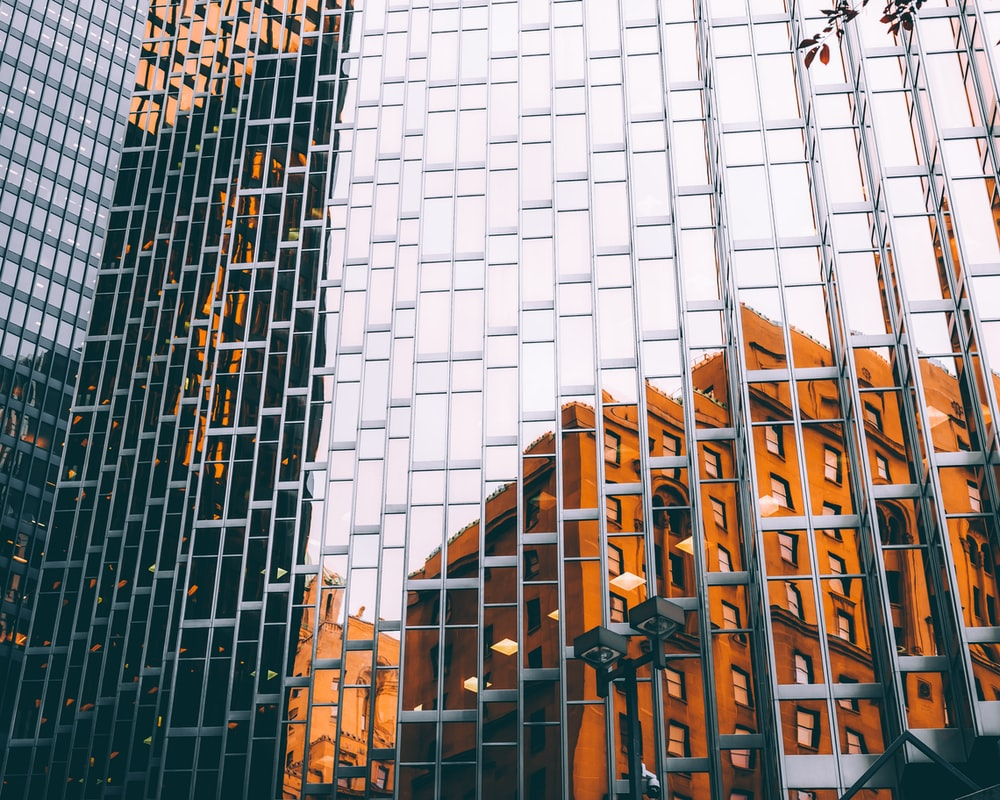 mirror building with reflection of orange painted building