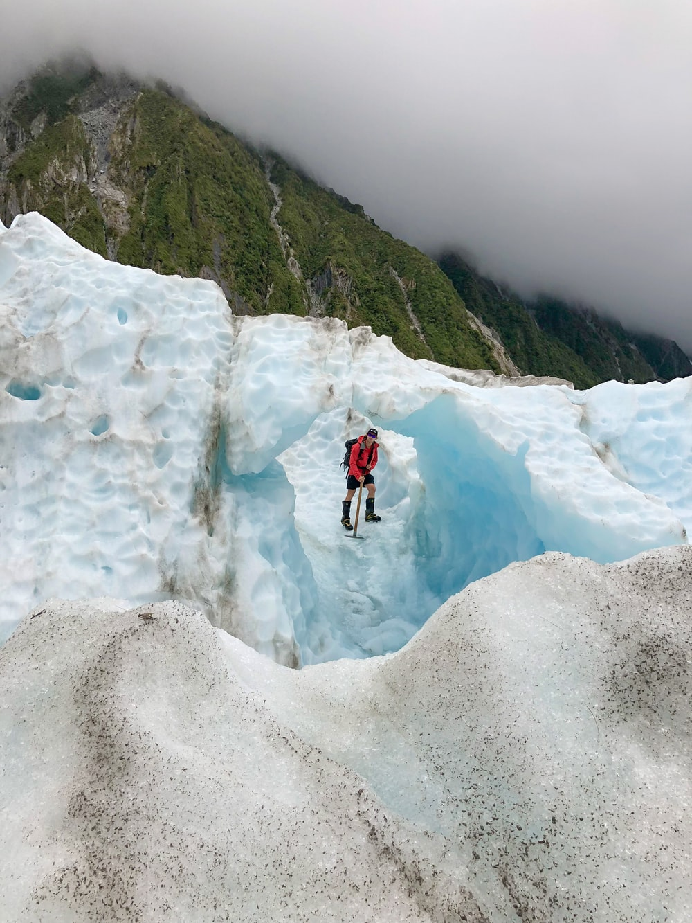person standing on ice hill