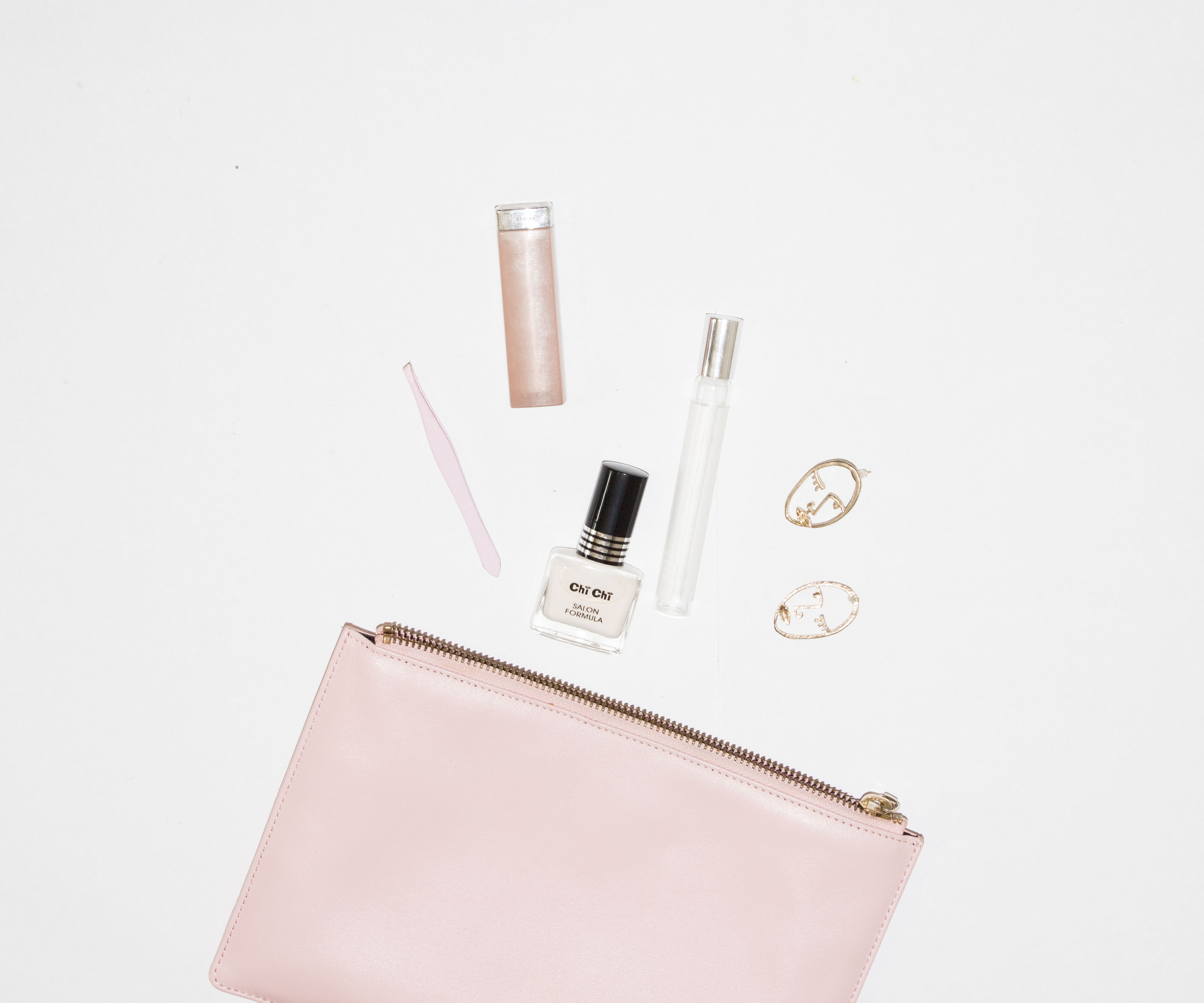 white nail polish bottle and pink leather zip pouch